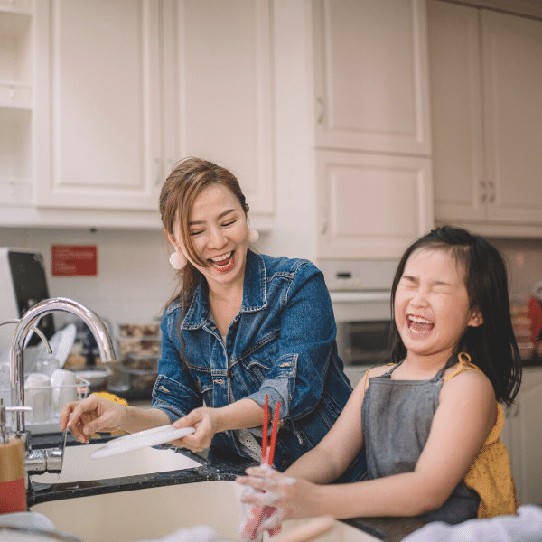 girl washing dishes with mother